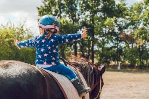 how dangerous is horseback riding for kids? Child on horse wearing helmet