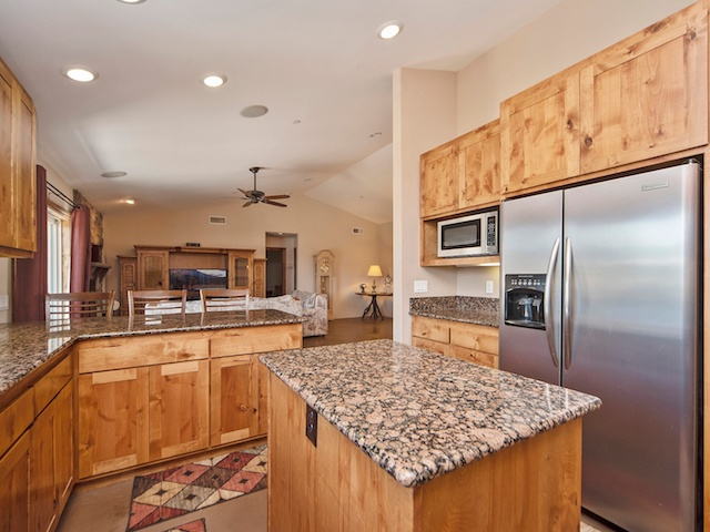 Norco Horse Town USA - house for sale with horse property and rustic barn for $599k, view of the kitchen with stainless steel fridge, wood cabinets, and granite